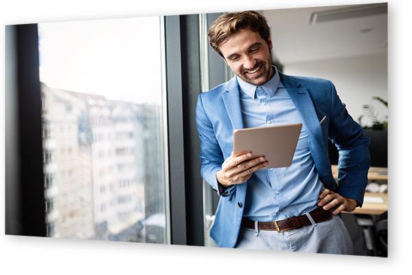 Mann in Sakko schaut auf Tablet